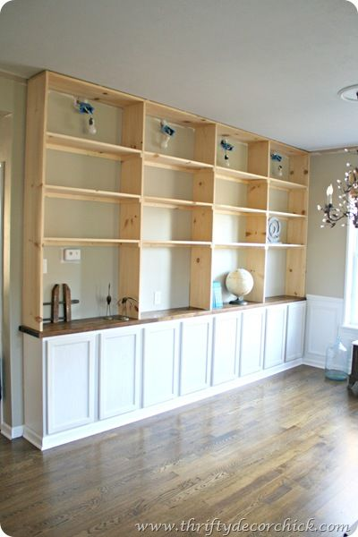 THRIFTY DECOR CHICK HAS AN INCRDIBLE TUTORIAL, IT ACTUALLY SEEMS LIKE SOMETHING I COULD TACKLE UTILIZING PRE MADE KITCHEN CABINETS AND TOPPING THEM WITH SHELVES.