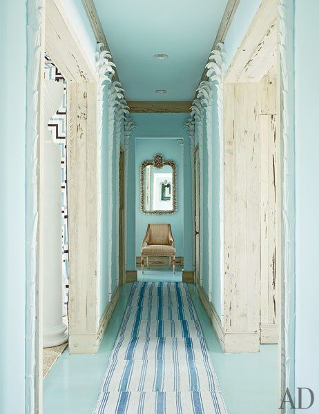 Architectural Digest - Miles Redd -A hallway, painted in Benjamin Moore's Clear Skies, is lined with plaster palm trees. Rugs from IKEA were stitched together to make the runner.